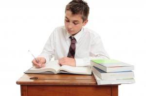 Un élève studieux sur son bureau en bois